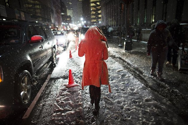 Snow falls on a pedestrian as she leaves the Rag & Bone Fall 2013 fashion collection show during Fashion Week, Friday, Feb. 8, 2013, in New York. Snow began falling across the Northeast on Friday, ush
