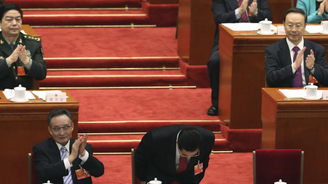 China's former President Hu Jintao, center, bows as former chairman of the Standing Committee of the National People's Congress Wu Bangguo, front left, applauds at the closing session of the National People's Congress at the Great Hall of the People in Beijing, China, Sunday, March 17, 2013.  China's new leader Xi Jinping pledged a cleaner, more efficient government Sunday as the country's ceremonial legislature wrapped up a pivotal session that installed the latest generation of communist leaders in a once-a-decade transfer of power.   (AP Photo/Kin Cheung)