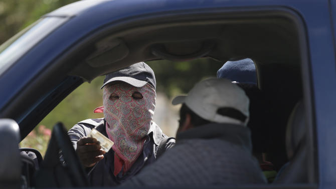 In this photo taken Jan. 18, 2013, a masked armed man checks the identity of a driver at a roadblock at the entrance to the town of El Pericon, near Ayutla, Mexico, Friday, Jan. 18, 2013. Hundreds of men in the southern Mexico state of Guerrero have taken up arms to defend their villages against drug gangs, a vigilante movement born of frustration at extortion, killings and kidnappings that local police are unable, or unwilling, to stop. (AP Photo/Dario Lopez-Mills)