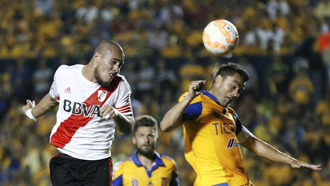 Jonathan Maidana of Argentina's River Plate jumps for the ball with Juninho of Mexico's Tigres during the first leg of their Copa Libertadores final soccer match