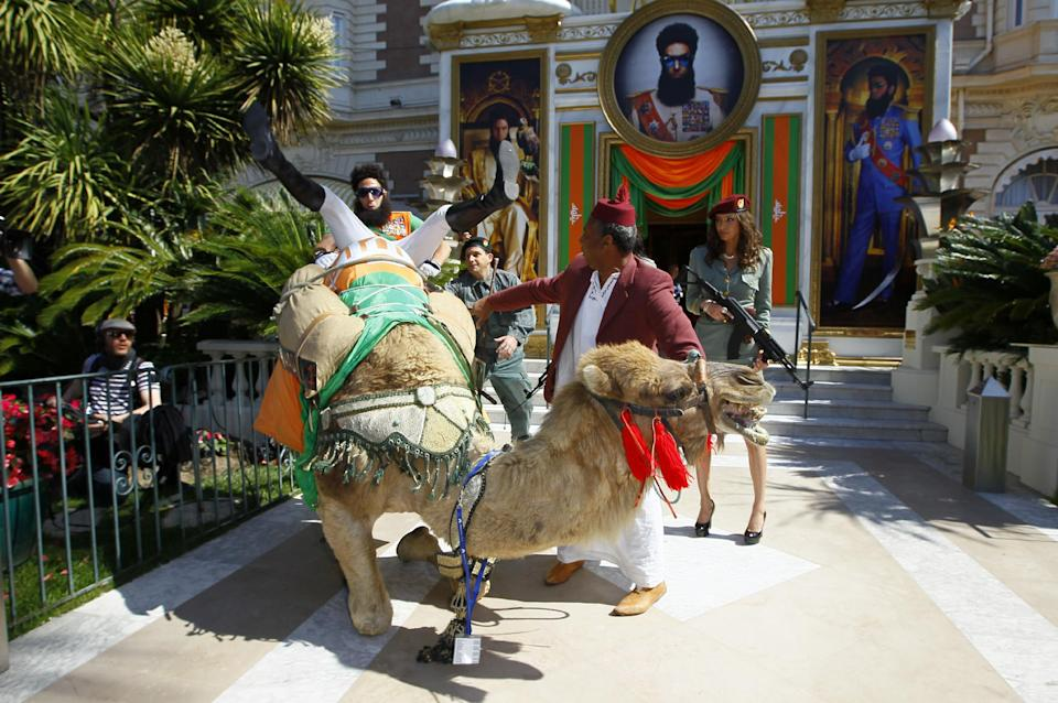 Actor Sacha Baron Cohen, loses balance on top of a camel as he poses during a photo call for The Dictator at the 65th international film festival, in Cannes, southern France, Wednesday, May 16, 2012. (AP Photo/Francois Mori)