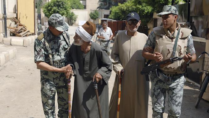 Egyptian soldiers help elderly voters after they cast their votes at a polling station in Zagazig, 62 miles (100 kilometers) northeast  of Cairo, Egypt, Saturday, June 16, 2012. Egyptians voted Saturday in the country's landmark presidential runoff, choosing between Hosni Mubarak's ex-prime minister and an Islamist candidate from the Muslim Brotherhood after a race that has deeply polarized the nation. The two-day balloting will produce Egypt's first president since a popular uprising last year ousted Mubarak, who is now serving a life sentence. (AP Photo/Amr Nabil)