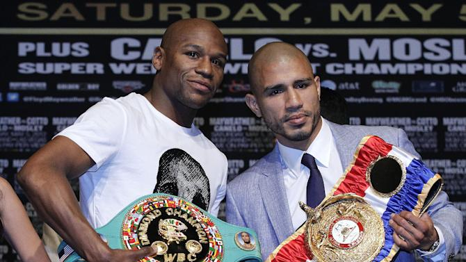 Floyd Mayweather, left, and Miguel Cotto pose for a photo during a news conference Wednesday, May 2, 2012, in Las Vegas. Mayweather and Cotto are scheduled to box for a super welterweight title on Saturday. (AP Photo/Julie Jacobson)