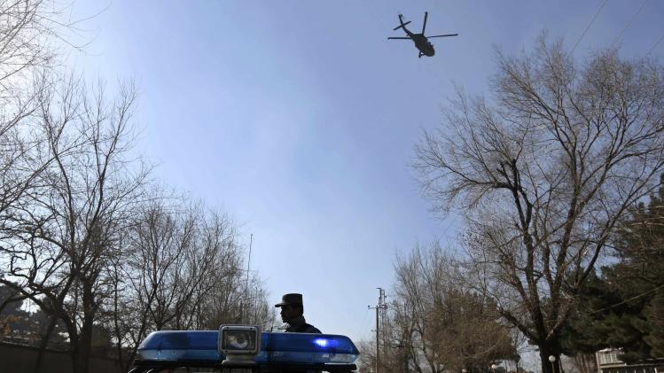 A NATO helicopter flies over the site of an explosion while an Afghan policeman keeps watch in Kabul