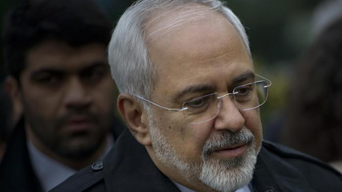 Iranian Foreign Minister Javad Zarif, walks through a courtyard at the Beau Rivage Palace Hotel during an extended round of talks, Wednesday, April 1, 2015 in Lausanne, Switzerland. Negotiations over Iran's nuclear program appeared headed for double overtime on Wednesday, beset by competing claims after diplomats abandoned a March 31 deadline for the outline of a deal and agreed to press on. (AP Photo/Brendan Smialowski, Pool)