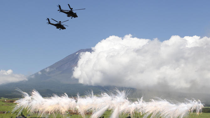 FILE - In this Aug. 21, 2012 file photo, two helicopters fly over a line of Japan Ground Self-Defense Force tanks flaring up a smoke screen during the annual live-firing exercise and demonstration at Higashi Fuji training range in Gotemba, southwest of Tokyo. Japan's military is kept on a very short leash under a war-renouncing constitution written by U.S. officials whose main concern was keeping Japan from rearming soon after World War II. But if Japan's soon-to-be prime minister Shinzo Abe has his way, the status quo may be in for some change. (AP Photo/Koji Sasahara, File)