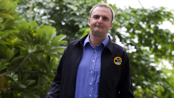 British human rights activist Andy Hall arrives at Phra Khanong provincial court for a trial in Bangkok, Thailand Tuesday, Sept. 2, 2014. Hall, who investigated alleged abuses at a Thai fruit processing factory went on trial Tuesday in the first in a series of criminal lawsuits filed against him by the company. Natural Fruit Co. Ltd. is accusing Hall of defamation in the wake of a report he helped author last year for the Finland-based watchdog group Finnwatch that detailed poor labor conditions in seafood and pineapple export companies in Thailand.(AP Photo/Sakchai Lalit)