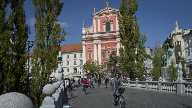 """Cyclists cross a bridge in downtown Ljubljana, Slovenia, Tuesday, Sept. 25, 2012. Once the envy of the former European communist states because of its booming economy and Western-style living standards, Slovenia is becoming a showcase of failed transition, government mismanagement and bad loans. Andrej Plut has always thought he was fortunate to live in Slovenia, at one time the most prosperous of the former republics of Yugoslavia and a star among the eastern European states that joined the EU after the fall of communism. The 55-year-old dentist can't figure out what went wrong with his tiny Alpine state, which now faces one of the worst recessions and financial system collapses among the crisis-stricken 17-country group that uses the euro. """"We used to live so well,"""" Plut said. """"Now, we don't know what tomorrow brings."""" (AP Photo/Darko Bandic)"""