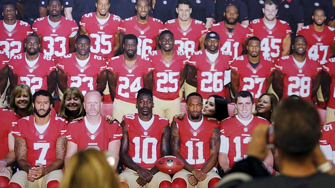Football fans pose with cardboard cut-outs of the San Francisco 49ers football team as they visit the NFL Experience in San Francisco