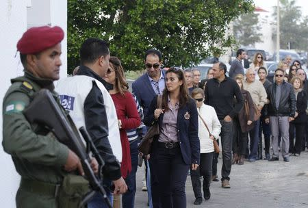 People queue outside a polling station during Tunisia's presidential election in Sousse