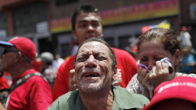 AP10ThingsToSee - A man screams as the coffin of Venezuela's late President Hugo Chavez passes in the street as it is paraded from the hospital, where he died on Tuesday, to a military academy where it will remain until his funeral in Caracas, Venezuela, Wednesday, March 6, 2013. Seven days of mourning were declared, all schools were suspended for the week and friendly heads of state were expected for an elaborate funeral Friday. (AP Photo/Rodrigo Abd, File)