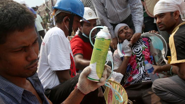 In this photo taken on Saturday April 27, 2013  volunteer workers help their colleagues as they were experiencing a sudden loss of Oxygen when trying to help with rescue work. When the Rana Plaza, a garment factory building collapsed, many of the first responders were neighborhood residents, fellow garment workers, relatives of the missing and charity workers, and they repeatedly took some of the most dangerous work.(AP Photo/Wong Maye-E)
