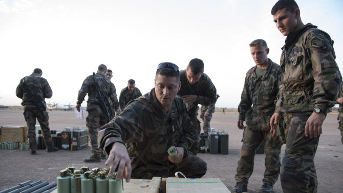 "In this picture dated Sunday, Jan. 13, 2013 and released by the French Army Communications Audiovisual office (ECPAD)  a French soldier of the 2nd Marine Infantry Regiment based in Le Mans, western France, distributes smoke grenades at Bamako airport, Mali. An official at France's Defense Ministry says the country will ""gradually deploy"" a total of 2,500 troops to Mali, and the French president says the military operation will last until security has been restored and African forces are ready to take charge. (AP Photo/Arnaud Roine, ECPAD)"