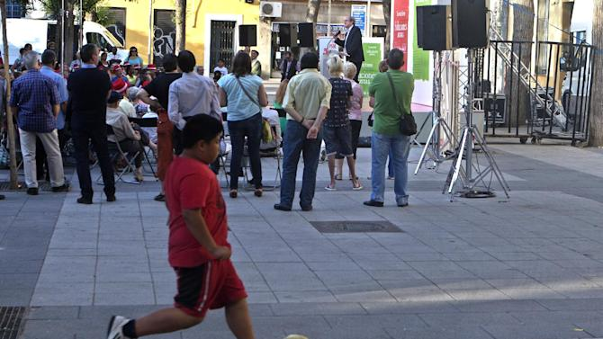 EDS NOTE : SPANISH LAW REQUIRES THAT THE FACES OF MINORS ARE MASKED IN PUBLICATIONS WITHIN SPAIN. In this  Monday, May 18, 2015 photo, a boy plays soccer while Socialist candidate for Madrid Angel Gabilondo makes a speech during an election rally in Madrid. Spain could be set for a political upheaval in key local elections this weekend, with strong signs that voters fed up with economic crisis and corruption scandals may punish both the ruling conservative Popular Party and the leading opposition Socialists. (AP Photo/Paul White)