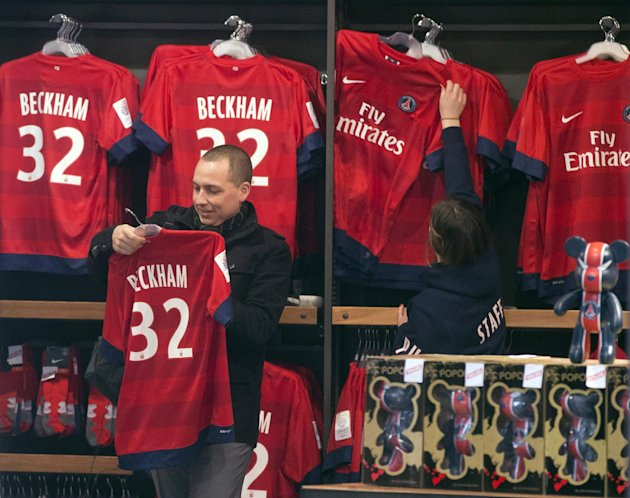 ADDS THE NAME OF THE CLUB A man looks at a soccer shirt on display with the name of British soccer player David Beckham, at the the Paris Saint-Germain club's shop on the Champs Elysees, in Paris, Fri