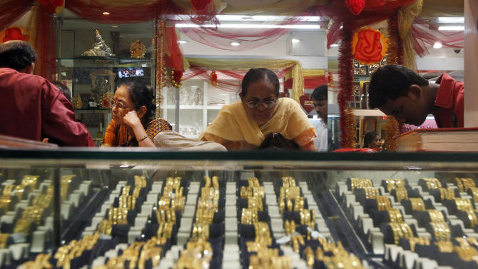 TO GO WITH STORY: INDIA GOLD RUSH BY KAY JOHNSON- In this Thursday, Feb. 14, 2013 photo, an Indian woman looks at a display of gold jewelry at a shop in Mumbai, India. Nowadays, India is by far the world's biggest buyer of gold, which despite its rising value, is an increasing drain on an economy that is growing too slowly to reduce widespread poverty. Last year Indians imported 864 tons of gold, about one fifth of world sales. The cost of 2.5 trillion rupees ($45 billion) was second only to India's bill for oil imports. The unquenchable appetite for gold coins, bars and jewelry has swelled India's trade deficit and weakened its currency, making crucial imports such as fuel more expensive. (AP Photo/Rajanish Kakade)