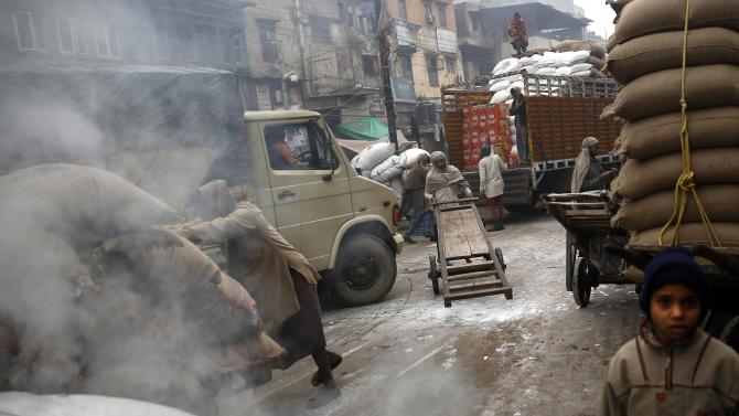 Labourers work at a wholesale grocery market on a winter morning in Delhi