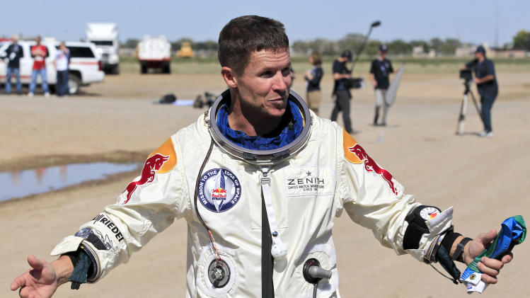Felix Baumgartner, of Austria, gestures prior to speaking with the media after successfully jumping from a space capsule lifted by a helium balloon at a height of just over 128,000 feet above the Earth's surface, Sunday, Oct. 14, 2012, in Roswell, N.M. (AP Photo/Ross D. Franklin)