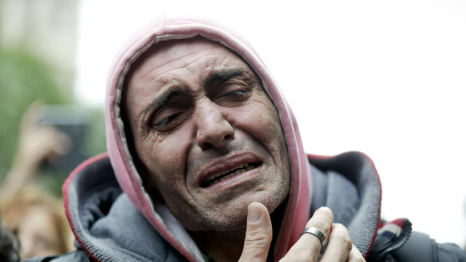 In this Friday, Sept. 5, 2014 photo, a man cries as mourners wait for the departure of the funeral car transporting the remains of Argentine rock star Gustavo Cerati to a cemetery, in Buenos Aires, Argentina. Cerati died on Thursday, four years after a stroke put him in a coma and ended the career of one of Latin America's most influential musicians. (AP Photo/Victor R. Caivano)