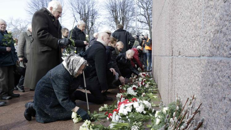 People put flowers at Freedom monument during annual procession commemorating Latvian Waffen-SS unit in Riga