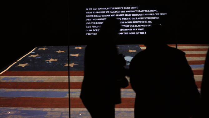 FILE - In this Nov. 21, 2008 file photo, people look at the original Star Spangled Banner, the flag that inspired the national anthem, inside a protective chamber at the National Museum of American History  in Washington. Whether visitors want to try one of the first family's favorite restaurants, discover a sense of history or escape from the crowd to find a museum off the beaten path, Washington is the nation's cultural capital this weekend for inauguration visitors. (AP Photo/Jacquelyn Martin, File)