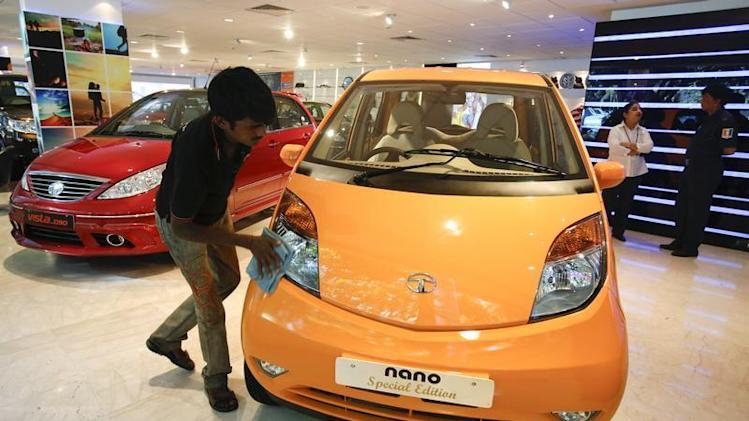 A showroom attendant cleans a Tata Nano car at their flagship showroom in Mumbai