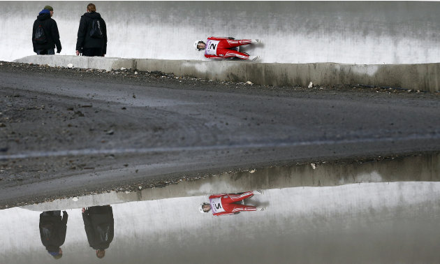 "Course workers look at Switzerland's Martina Koch speeding down the track during the women's luge World Cup at the ""Sanki"" sliding center in the winter sport resort of Rosa Khutor, a venue for the Soc"