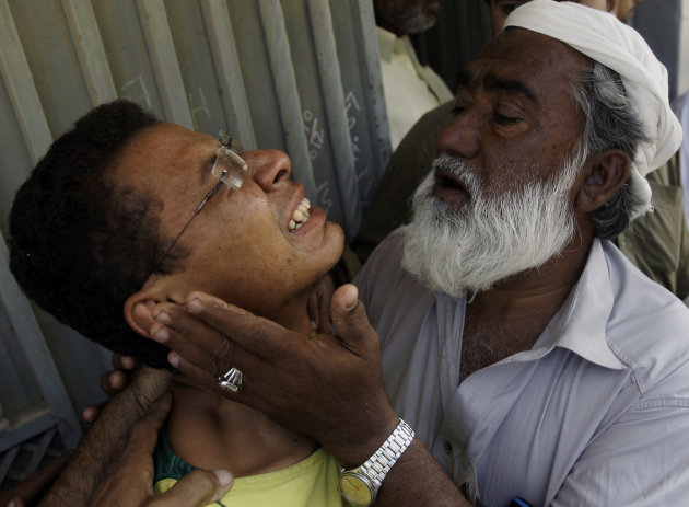 An unidentified man comforts Ali Mohammad, mourning the death of his father killed in a bomb blast, outside his residence in Karachi, Pakistan on Monday, Nov. 26, 2012. A bomb hidden in a cement const