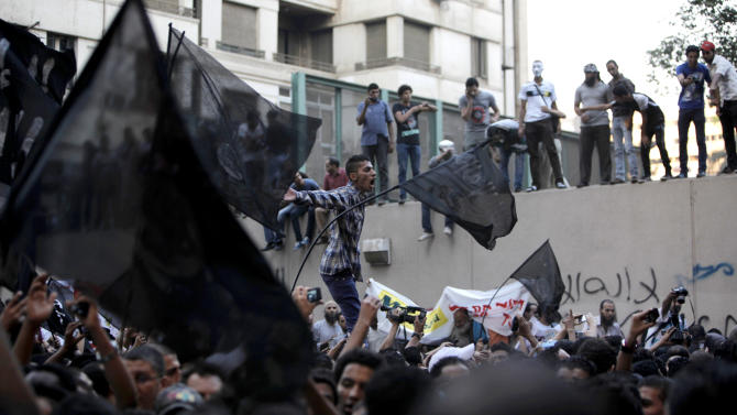 """Egyptian protesters climb the walls of the U.S. embassy while others chant anti U.S. slogans during a protest in Cairo, Egypt, Tuesday, Sept. 11, 2012. Egyptian protesters, largely ultra conservative Islamists, have climbed the walls of the U.S. embassy in Cairo, went into the courtyard and brought down the flag, replacing it with a black flag with Islamic inscription, in protest of a film deemed offensive of Islam. Arabic graffiti reads """"Their is only one God."""" (AP Photo/Nasser Nasser)"""