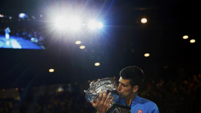 Djokovic of Serbia kisses his trophy after defeating Murray of Britain in their men's singles final match at the Australian Open 2015 tennis tournament in Melbourne