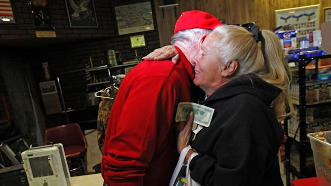 Carol Hefty hugs Secret Santa after he gave her a $100 dollar bill while she was looking for supplies at a temporary supply house at the Oakwood Heights VFW Post 9587 in the boro of Staten Island, New York, N.Y., Thursday, Nov. 29, 2012. The wealthy philanthropist from Kansas City, Mo. Secret Santa distributed $100 dollar bills to needy people at several locations in Elizabeth, N.J. and Staten Island. (AP Photo/Rich Schultz)