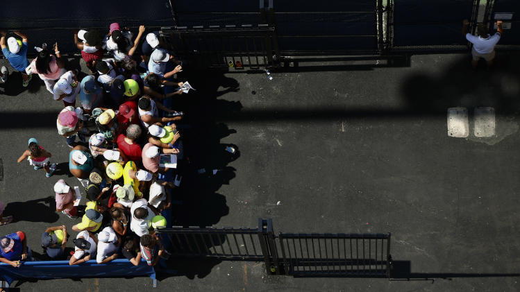 Tennis fans wait outside the practice courts for autographs from players during the second round of the 2014 U.S. Open tennis tournament, Wednesday, Aug. 27, 2014, in New York. (AP Photo/Matt Rourke)