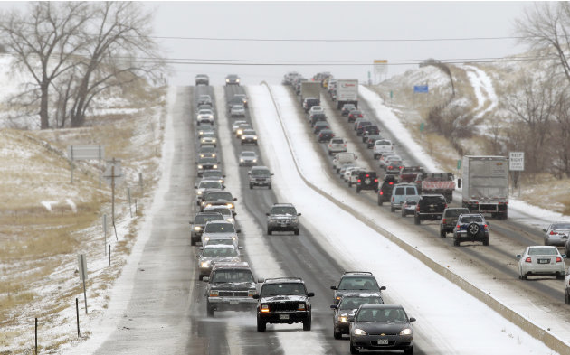 Traffic winds its way east and west along a snowy Boulder-Denver Turnpike, in Superior, Colo., Wednesday Dec. 19, 2012. A storm that has dumped more than a foot of snow in the Rocky Mountains is headi