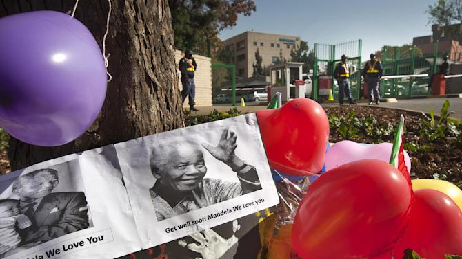 "Balloons, hand-prints and get well messages left by children from the ""Ring-Ting"" kindergarten lie outside the entrance to the Mediclinic Heart Hospital where former South African President Nelson Mandela is being treated in Pretoria, South Africa Friday, June 14, 2013. Nelson Mandela's health is improving but the 94-year-old beloved anti-apartheid hero remains in serious condition, South Africa's president said Thursday. (AP Photo/Ben Curtis)"