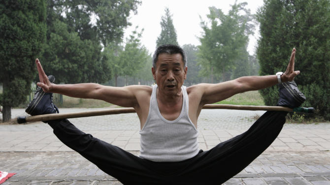A man stretches himself during a morning exercise session at a park in Beijing