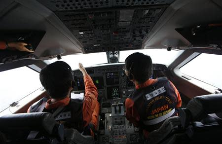 Japan Coast Guard pilots look out from the cockpit of their Gulfstream V Jet aircraft as they search for the missing Malaysia Airlines MH370 plane over the South China Sea