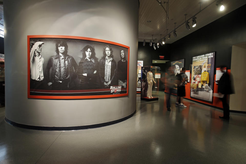 "In this May 21, 2013 photo, a large photo of the Rolling Stones dominates an exhibit space at the Rock and Roll Hall of Fame in Cleveland. The new exhibit ""Rolling Stones 50 Years of Satisfaction"" opens Friday. (AP Photo/Mark Duncan)"