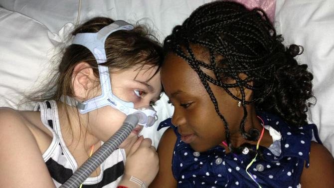 FILE - In this May 30, 2013 file photo provided by the Murnaghan family, Sarah Murnaghan, left, lies in her hospital bed next to her sister Ella on the 100th day of her stay in Children's Hospital of Philadelphia. Murnaghan, who got adult lungs after her parents sued to change national transplant rules, is scheduled to have more surgery to repair her diaphragm at Children's Hospital of Philadelphia, Tuesday, July 2, 2013. That's according to a post on the Facebook page of her mother, Janet Murnaghan. (AP Photo/Murnaghan family, File)