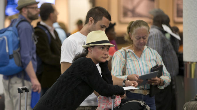Sulien Brezzo, from France, waits in line to rebook her flight to New York at the Miami International Airport, Tuesday, April 16, 2013. She had already stood in line for two hours and still had a long wait until she got to the ticket counter. American Airlines says it has fixed an outage in its main reservations system that is disrupting travel for thousands of passengers whose flights have been delayed or canceled. Roughly 900 flights are directly impacted, according to flight tracking site FlightAware, with another 800 indirectly impacted due to planes and crew being out of place.  (AP Photo/J Pat Carter)