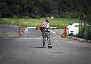 An armed pro-Russian separatist guards a border post …
