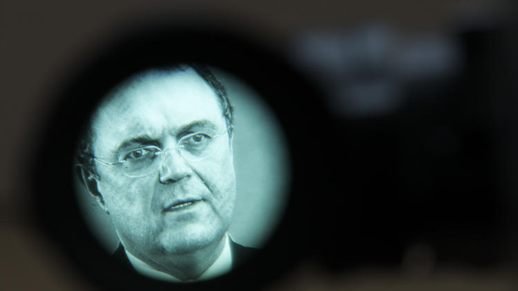 German Interior Minister Hans-Peter Friedrich seen through a television camera view finder as he briefs the media in Berlin, Wednesday, March 13, 2013. German authorities banned three ultraconservative Islamic groups Wednesday, including one whose Internet propaganda videos helped inspire the extremist who killed two American airmen at Frankfurt airport in 2011, the country's domestic intelligence chief Hans-Georg Maassen said.  Police launched early morning raids on 21 apartments and one meeting room belonging to DawaFFM, Islamic Audios and al-Nussrah - all of which adhere to the hardcore conservative Salafi interpretation of Islam. (AP Photo/Markus Schreiber)
