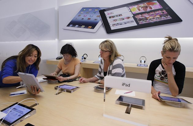 In this Thursday, July 19, 2012, photo, an Apple worker, left, gives a tutorial on Apple iPad to customers at an Apple store in Palo Alto, Calif. Apple Inc. reports quarterly financial results after the market closes on Tuesday, July 24. (AP Photo/Paul Sakuma)
