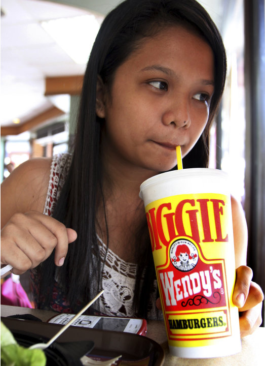 Pearl Ganotisi sips from her 24-ounce of soda drinks as she takes her meal in an American hamburger chain Friday, June 1, 2012 in Manila, Philippines.   New York Mayor Michael Bloomberg has proposed a