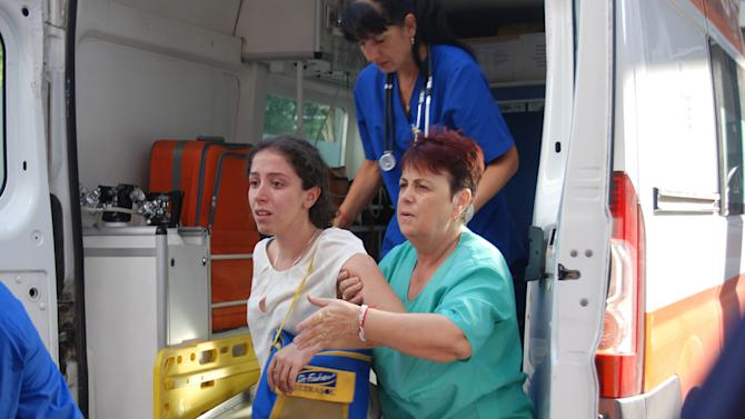 Unidentified Israeli tourist is helped as she arrives to Bourgas hospital after a bus carrying Israeli tourists in the Bulgarian resort city of Bourgas exploded Wednesday, July 18, 2012, killing at least three people and wounding more than 20 others, police said.  Israel says it is holding Iran responsible for the explosion on a bus carrying Israeli youths today at a resort in the Black Sea city of Burgas, some 400 kilometers (250 miles) east of the capital, Sofia.  (AP Photo/ Bulphoto Agency) BULGARIA OUT