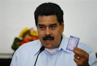 Venezuela's President Nicolas Maduro holds a copy of the country's constitution as he talks to the media during a news conference at the Miraflores Palace in Caracas September 9, 2013. REUTERS/Carlos Garcia Rawlins