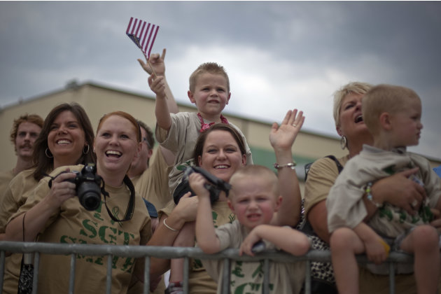 Rachel Smith, 23, center, of Clarksville, Tenn., holds her nephew Noah Jensen, 5, on top of her shoulders as she waits with family members for her husband, Sgt. Jeremy Smith, with the U.S. Army's 4th