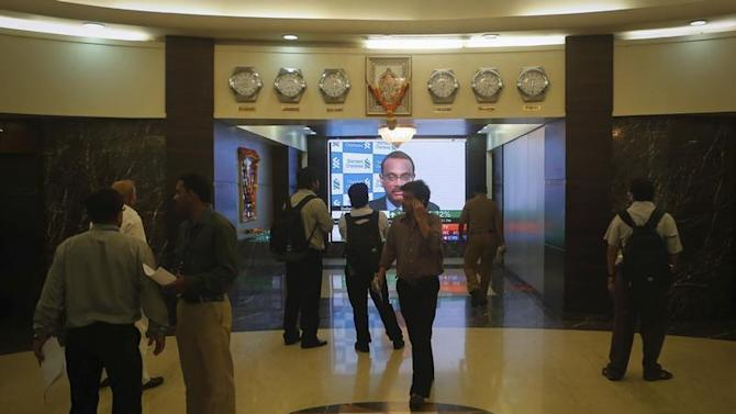 Employees stand in a lobby as they wait for the elevator inside Bombay Stock Exchange (BSE) building in Mumbai