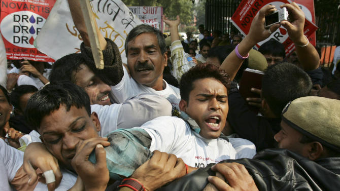 FILE – In this Jan. 29, 2007 file photo, Indian police officers block demonstrators protesting against Swiss drug maker Novartis AG's case against Indian government on drug patents in New Delhi, India. The case - involving Novartis AG's cancer drug Glivec - pits aid groups that argue India plays a vital role as the pharmacy to the poor against drug companies that insist they need strong patents to make drug development profitable. A ruling by India's Supreme Court is expected in early 2013. (AP Photo/Saurabh Das, File)