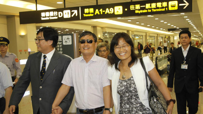 Arriving with his wife Yuan Weijing, Chinese activist Chen Guangcheng walks through Taipei International Airport in Taoyuan, Taiwan, Sunday, June 23, 2013. Chen, who fled house arrest in China and later moved to the U.S., arrived Sunday in Taiwan, where he will give several speeches over an 18-day stay, expecting to attract the attention of Beijing. (AP Photo/Wally Santana)