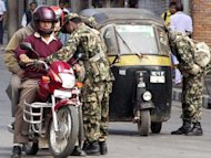 "Nepalese soldiers check a motorcycle and auto taxi during a strike called by Maoist rebels in Kathmandu, in November 2002. The makers of a film called ""Badhshala"" (Slaughterhouse) depicting torture by Nepal's army during the 1996-2006 civil war has accused the government of censorship after they had to cancel the movie's release because of delays in getting approvals"